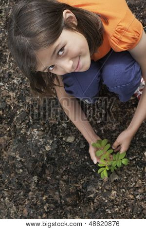 Elevated portrait view of a smiling girl planting black locust tree