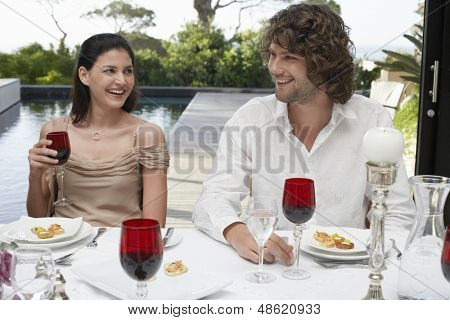 Happy young friends sitting near pool socialising at dinner party