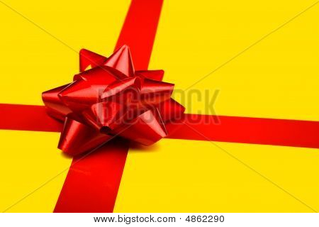 Red Holiday Bow On Yellow Background