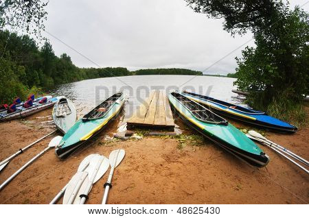 Canoes stand on a lake bank