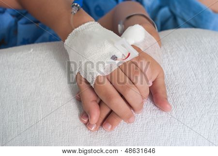 Asian Patient Boy Hand With Saline Intravenous (iv) On Hospital Bed.
