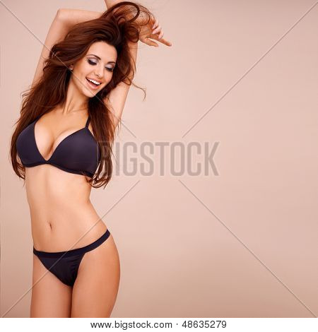 Sexy laughing woman in black lingerie raising her arms above her head  three quarter studio portrait on beige
