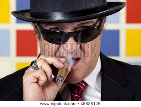 Middle aged repulsive businessman is smoking cigar.