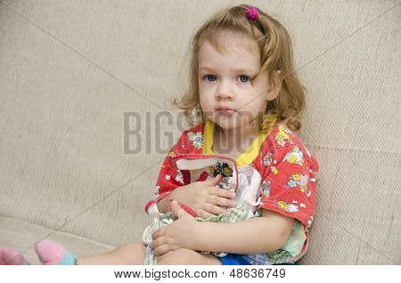 The little girl was sitting on the sofa with scarves in the hands of