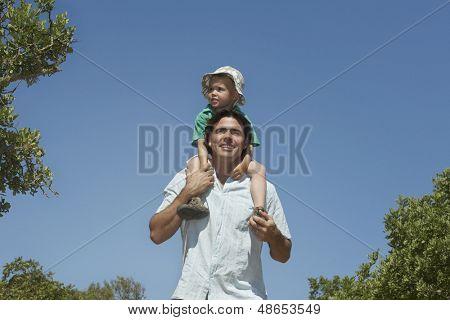 Lächelnd weiter tragenden Sohn auf Schultern gegen den klaren blauen Himmel