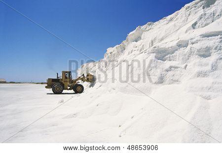 Bulldozer truck loading salt at refining plant