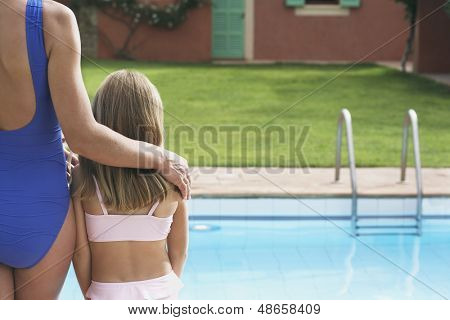 Rear view of cropped mother with daughter in swimwear by the pool