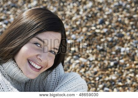 Portrait of happy young woman smiling while sitting at beach