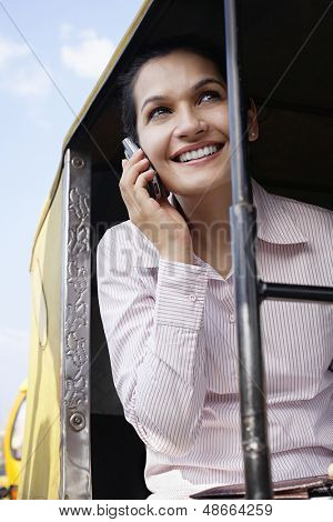 Smiling young businesswoman using cell phone in tuk-tuk taxi