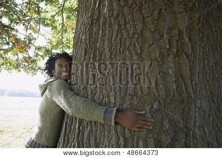 Happy young African American man looking away while embracing tree trunk at park