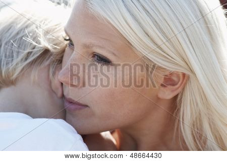 Closeup of blond young woman and son cheek to cheek
