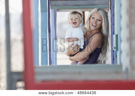 Portrait of beautiful young woman carrying baby boy at porch