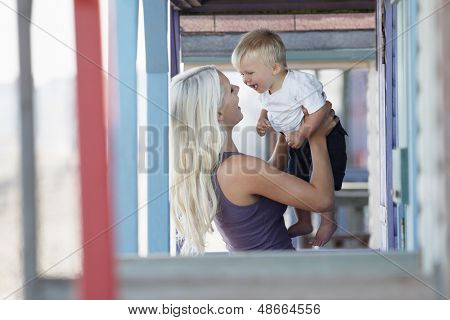 Cheerful woman playing with son at porch
