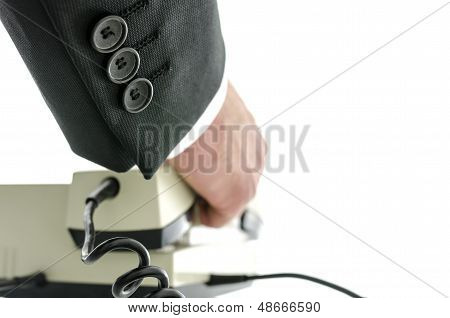 Rear View Of Businessman Picking Up The Phone