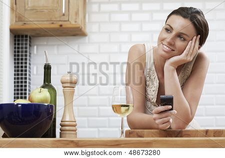 Thoughtful young woman holding cellphone while leaning on wooden counter in kitchen