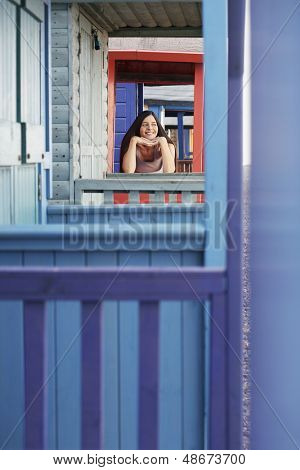 Beautiful young woman looking away while leaning on balustrade of beach house