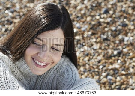 Closeup of beautiful young woman smiling while looking away at beach
