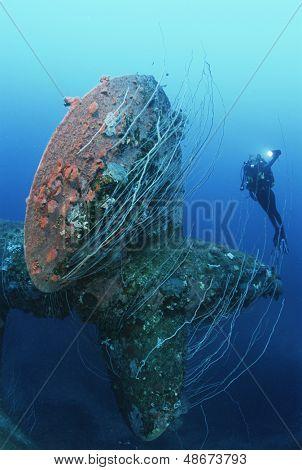 Underwater shoot of female scuba diver swimming near propeller of sunken battleship