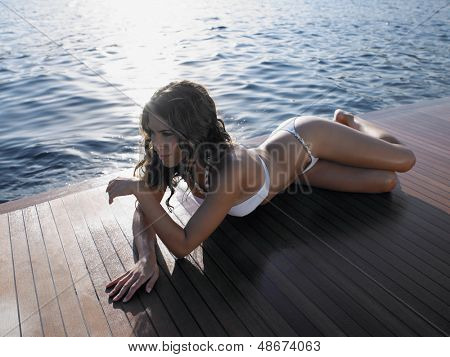 Sensuous woman in bikini looking away while sunbathing on yacht's floorboard