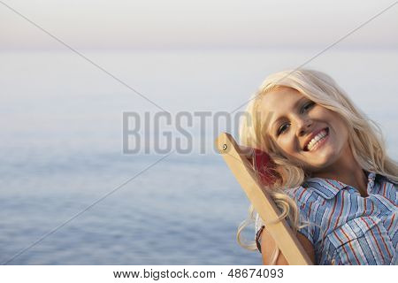 Portrait of beautiful young woman relaxing on desk chair at beach