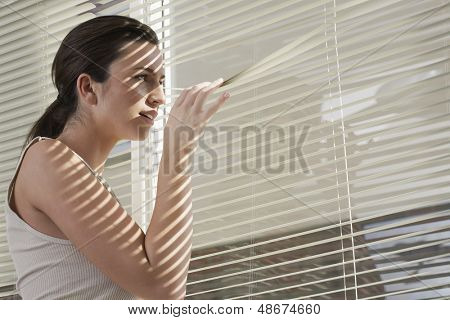 Side view of young woman peering through blinds at home