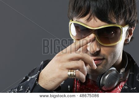 Closeup portrait of handsome young man adjusting sunglasses on gray background