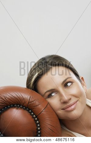 Close up of thoughtful young woman relaxing on sofa's armrest at home