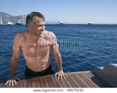 Middle aged man looking away while leaning on the edge of yacht's floorboard