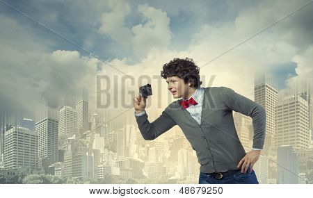 Image of young man in red tie with photo camera taking pictures