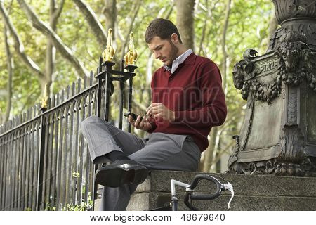 Young businessman using smartphone while sitting on wall outdoors