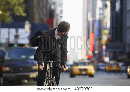 Young businessman looking over shoulder while riding bicycle on urban street