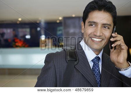 Closeup of confident young businessman using cell phone in hotel lobby