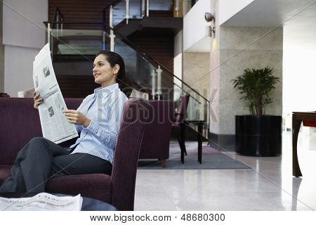 Happy young businesswoman reading newspaper in hotel lobby