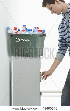 Young man filling glass of water from cooler with recycle bin on it