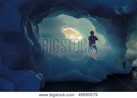 Rear view of little boy with arms outstretched standing inside iceberg