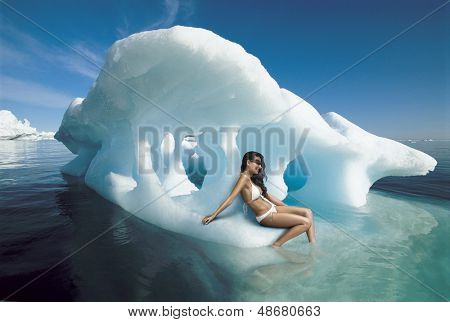 Beautiful young woman in bikini sitting on iceberg