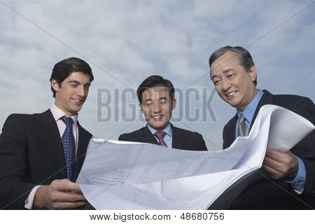 Three multiethnic business people looking at blueprint against cloudy sky