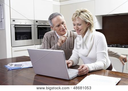 Happy middle aged couple calculating home finances on laptop at kitchen table