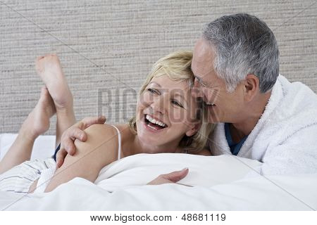 Cheerful middle aged couple lying in bed