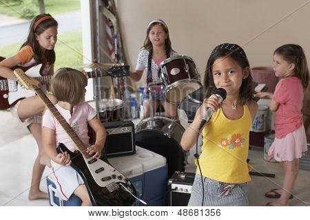 Portrait of cute young girl singing into microphone with friends playing musical instrument in garage