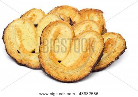 some palmeras, spanish palmier pastries, coated with chocolate in the back, on a white background