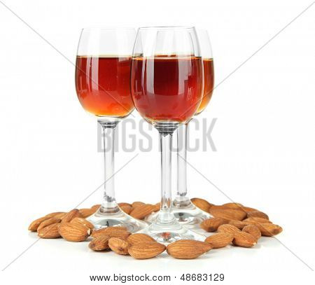 Glasses of amaretto liquor and roasted almonds, isolated on white