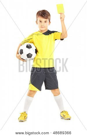Full length portrait of a kid in sportswear holding soccer ball and giving yellow card isolated on white background