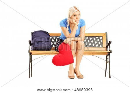 Disappointed blond female sitting on a wooden bench and holding a red heart isolated on white background