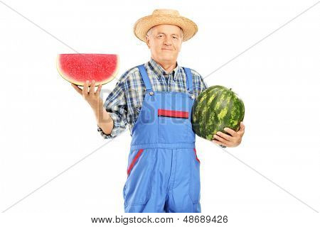 Smiling farmer in dungarees holding a watermelon and slice isolated on white background
