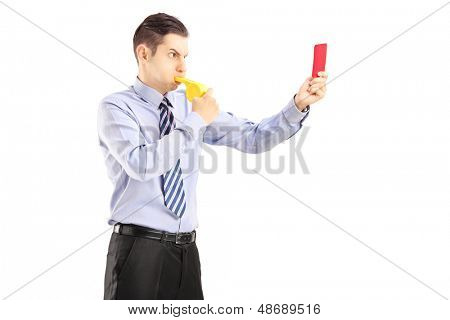 Young man blowing a whistle and showing a red card, isolated on white background