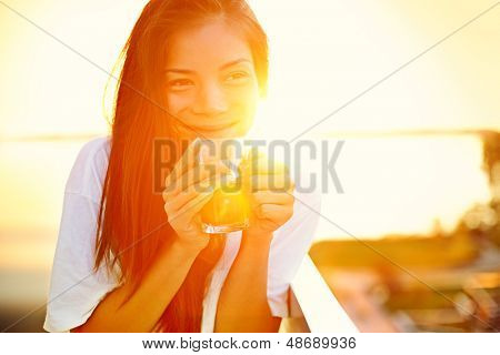 Asian woman drinking coffee in sun sitting outdoor in sunshine light enjoying her morning coffee. Smiling happy multiracial female Asian Chinese / Caucasian model in her 20s.
