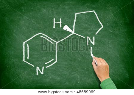 Nicotine. Chemical structure of nicotine from cigarettes written on blackboard by teacher in education of health. Nicotine molecule on green chalkboard.