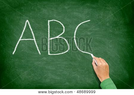 ABC, education and primary school blackboard concept. School teacher writing ABC alphabet in English class or preschool.on chalkboard.