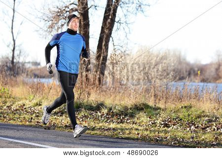 Male runner man running in autumn on cold day wearing long tights and long sporty jogging outfit. Fit male fitness athlete model training outdoor in fall. Full body length of jogger.
